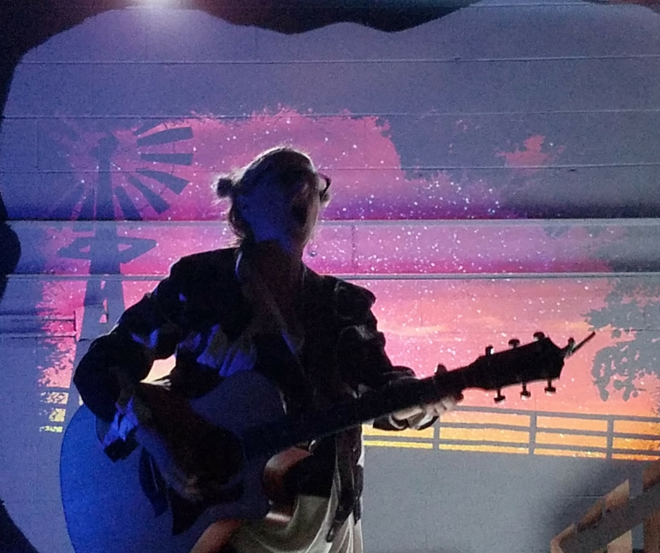 Gina Stewart agains the backdrop of projections by Marie Yokoyama in Click, Clack, Moo