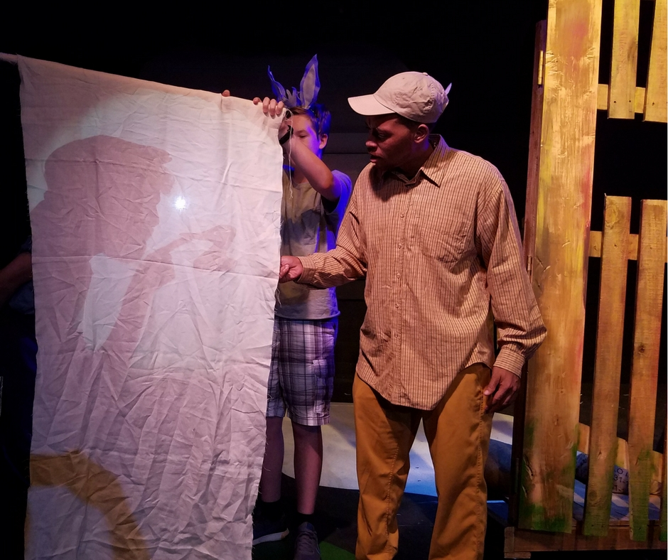Jonathan Santos performing Duck in person and in shadow during ACA's production of Click, Clack, Moo: Cows That Type