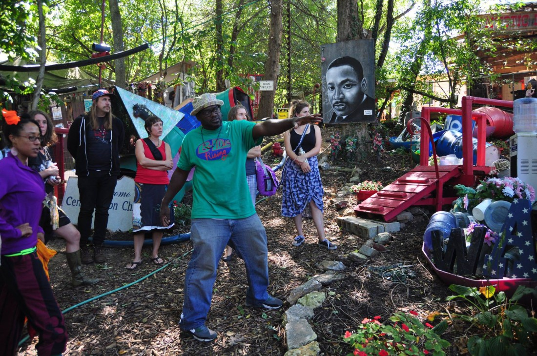 "GROWING THE ARTS: ""If the kids want to play basketball, they can go to that court over there, but what if they want to be a theater major or artist or performer?"" asks Hood Huggers International co-founder DeWayne Barton, center in green shirt. ""We want to create that structure in the neighborhood."" The collaborative Ancestors in the Garden event looks to provide such a solution."